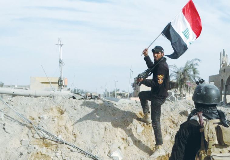 A MEMBER of Iraq's security forces holds an Iraqi flag in Ramadi on Sunday