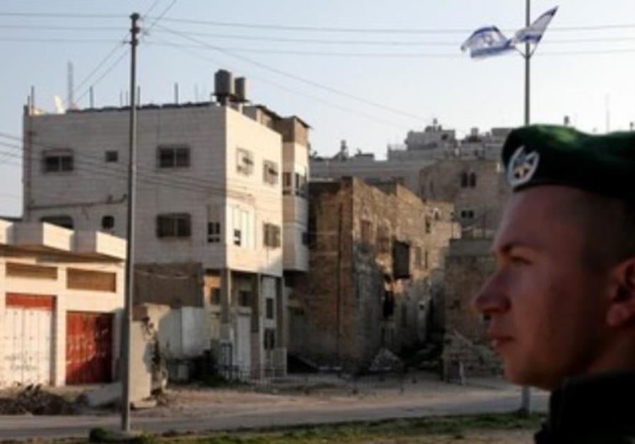 IDF soldier stands guard next to Beit Hamachpela