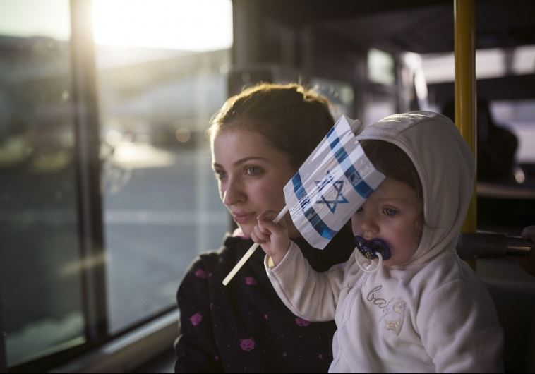 A Jewish immigrant from Ukraine holds her daughter aboard a bus