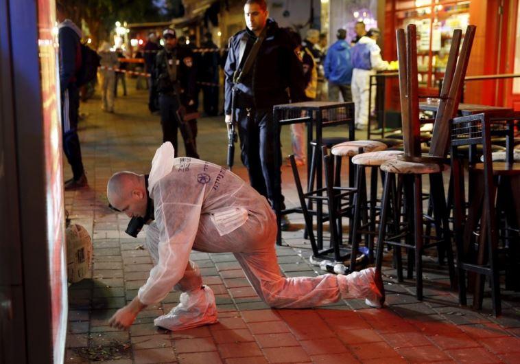 Israeli forensic policemen work at the scene of a shooting incident in Tel Aviv