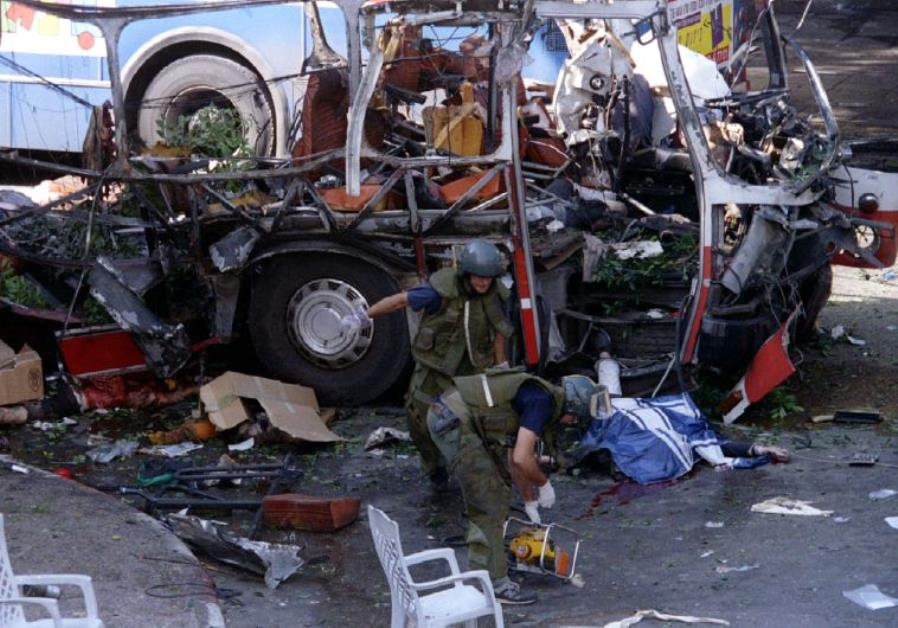 Police sappers work near a bus destroyed by a suicide bomber