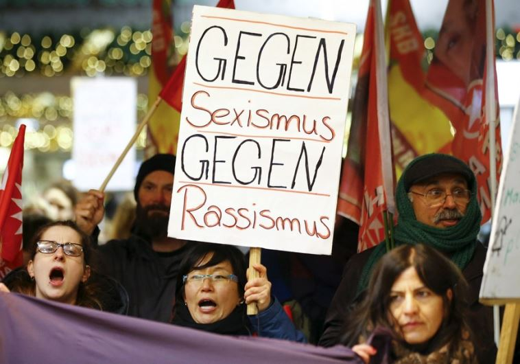 "Women shout slogans and hold up a placard that reads ""Against Sexism - Against Racism"""