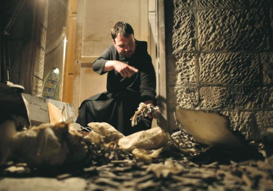 A PRIEST points to damage at the Dormition Abbey on Mount Zion after an arson attack on May 26, 2015