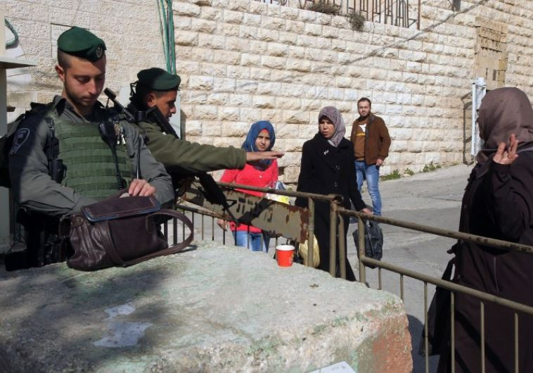Border Police officers stop Palestinian women to check their belongings at a checkpoint in Hebron