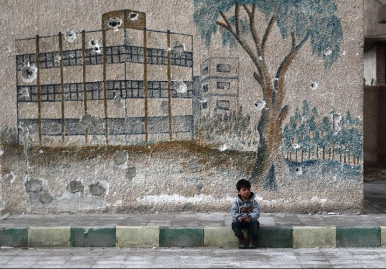 A Syrian child sits in front of a mural covered in bullet holes on the wall of a former school