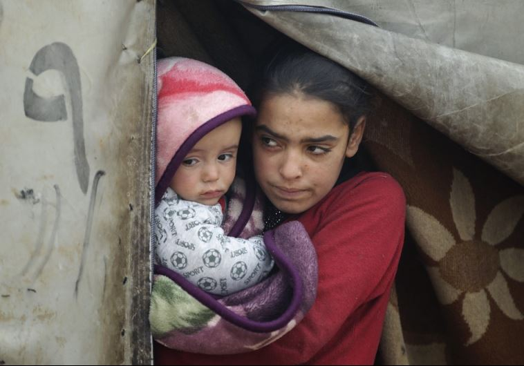 A girl carries her brother as she stands at the entrance of her tent during the cold weather