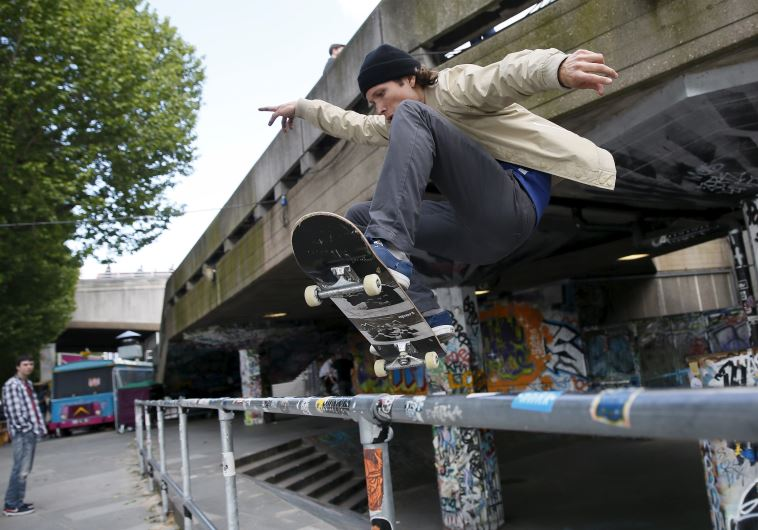 A skateboarder performs a jump over a railing