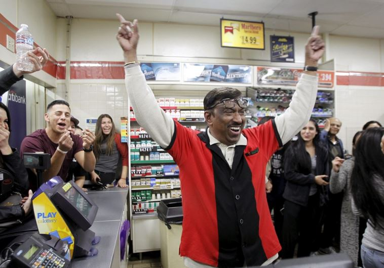 7-Eleven store clerk M. Faroqui celebrates after selling a winning Powerball ticket in Chino Hills