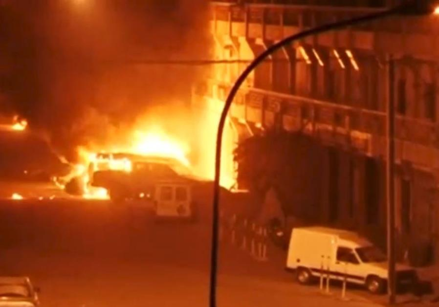 A view shows vehicles on fire outside Splendid Hotel in Ouagadougou, Burkina Faso in this still imag
