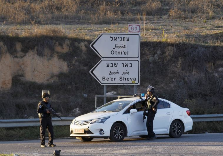 Israeli policemen stand near a checkpoint close to the West Bank settlement of Otniel