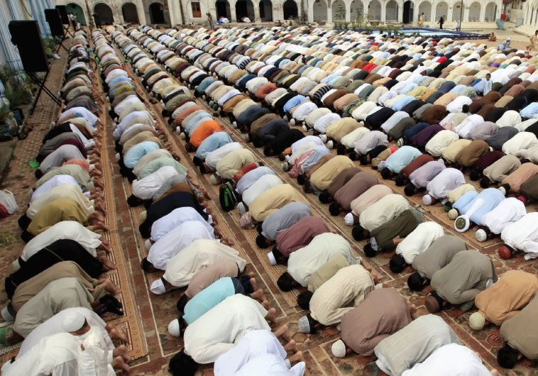 PAKISTANI MUSLIMS offer prayers on friday. The author argues that Palestinians he met were not very