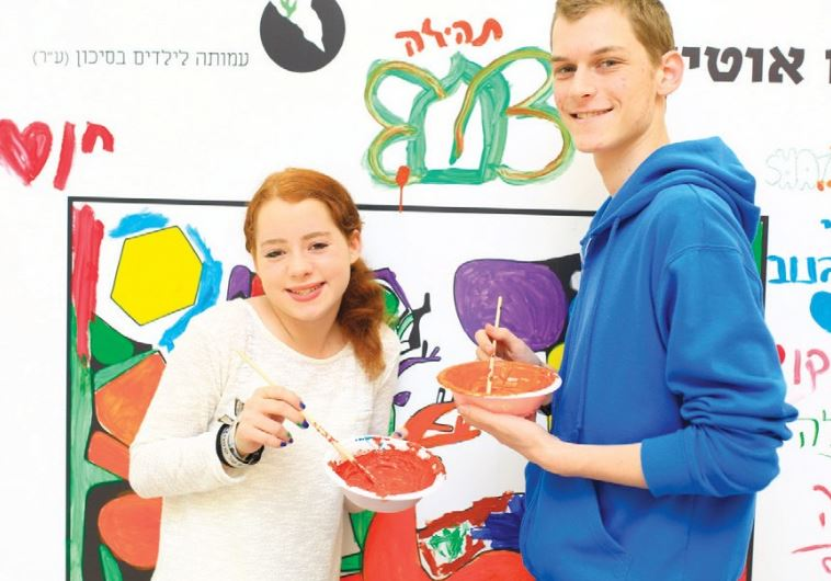 STUDENTS DAB PAINT onto a large coloring wall yesterday as part of a campaign launched by ALUT.