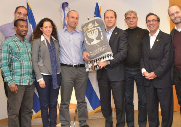 JERUSALEM MAYOR Nir Barkat holds a Torah that was donated in honor of Shira in a ceremony.