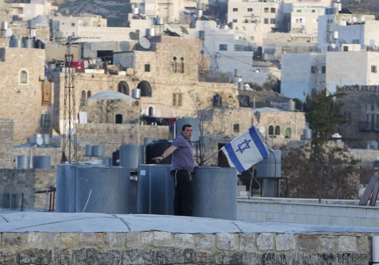 An Israeli settler puts up an Israeli flag over a house in Hebron