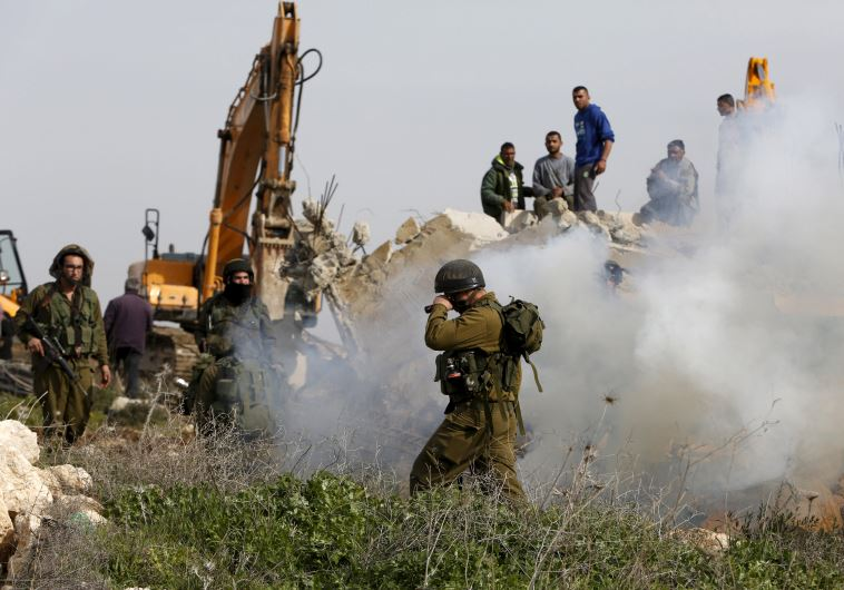 An Israeli soldier reacts to tear gas during the demolition of a Palestinian house