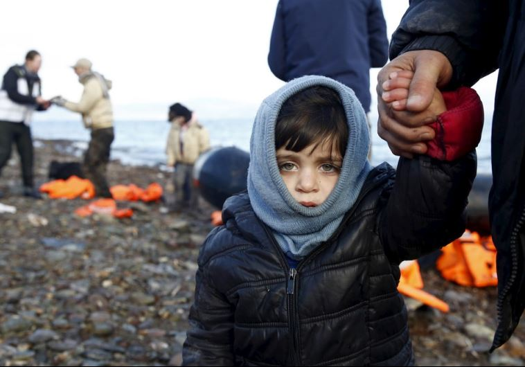 A Syrian refugee child looks on, moments after arriving on a raft with other Syrian refugees