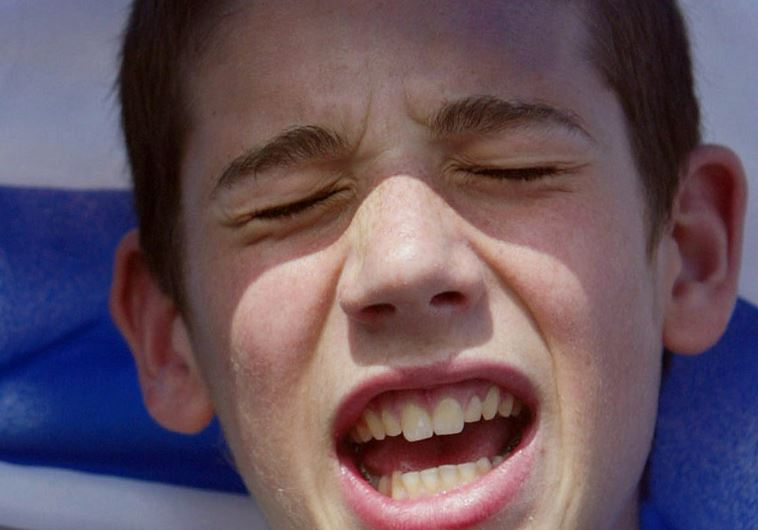 A boy sings underneath the Israeli flag at the Israel Solidarity Rally in London's Trafalgar Square