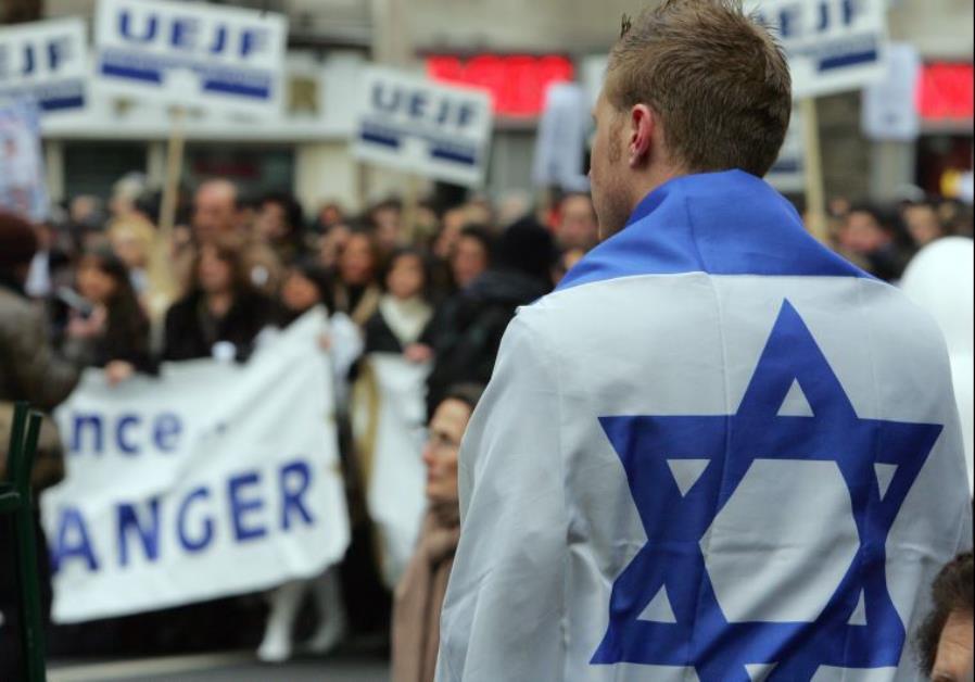 A man with an Israeli flag takes part in a march through Paris