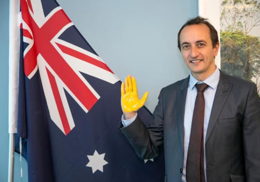 ustralian Ambassador to Israel Dave Sharma with his palm painted yellow to sign the virtual wall.