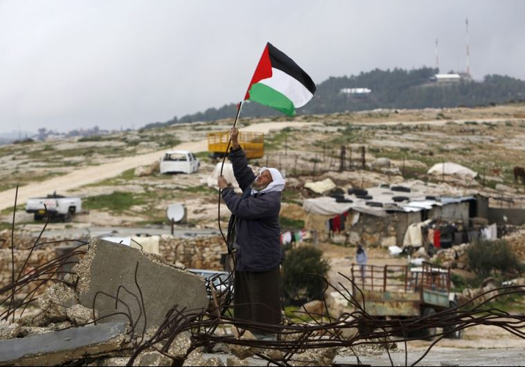 A Palestinian man hangs a Palestinian flag atop the ruins of a mosque