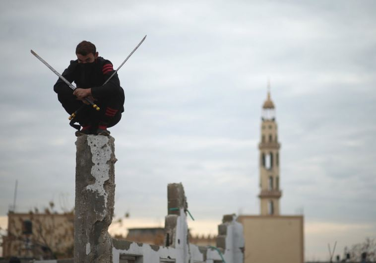 A Palestinian youth holds swords as he demonstrates his ninja-style skills for a photographer