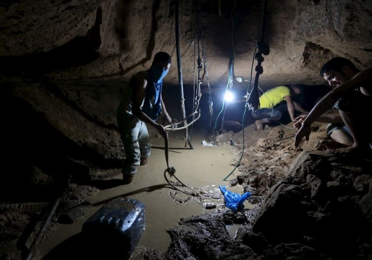 Palestinians work to repair a smuggling tunnel, that was flooded by Egyptian security forces