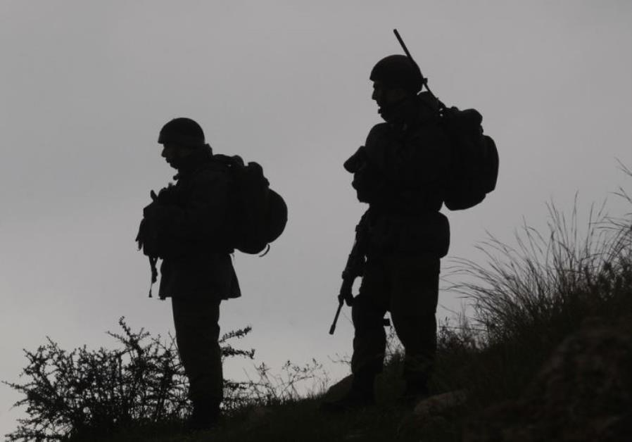 IDF soldiers stand guard during a demonstration by Palestinians
