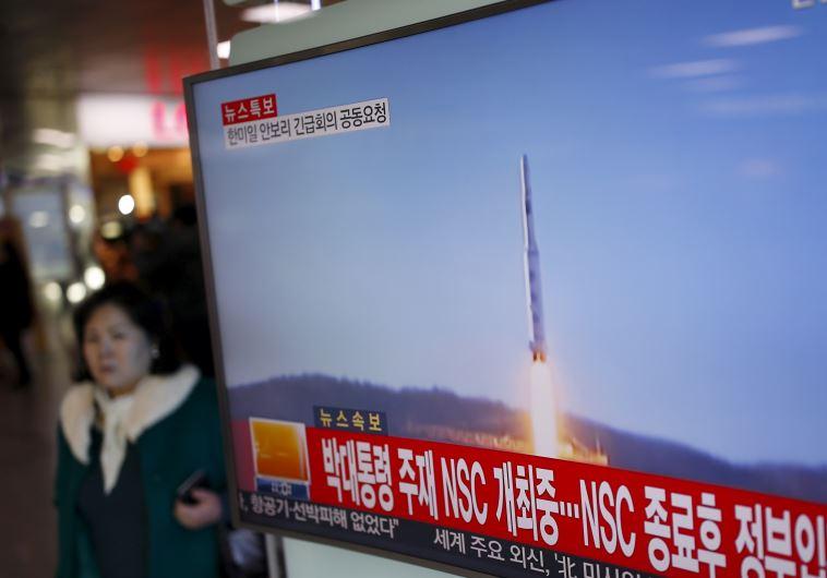 A passenger walks past a TV screen broadcasting a news report on North Korea's long range rocket lau