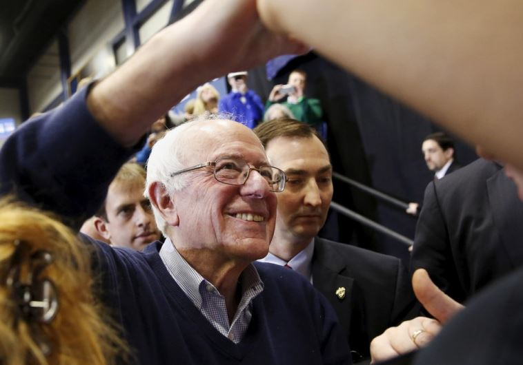 Democratic US presidential candidate Bernie Sanders shakes hands with supporters during a rally