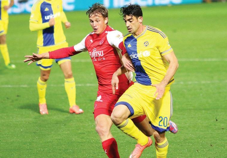 Hapoel Tel Aviv goal-scorer Aaron Schoenfeld (left) battles Maccabi Tel Aviv's Omri Ben-Harush