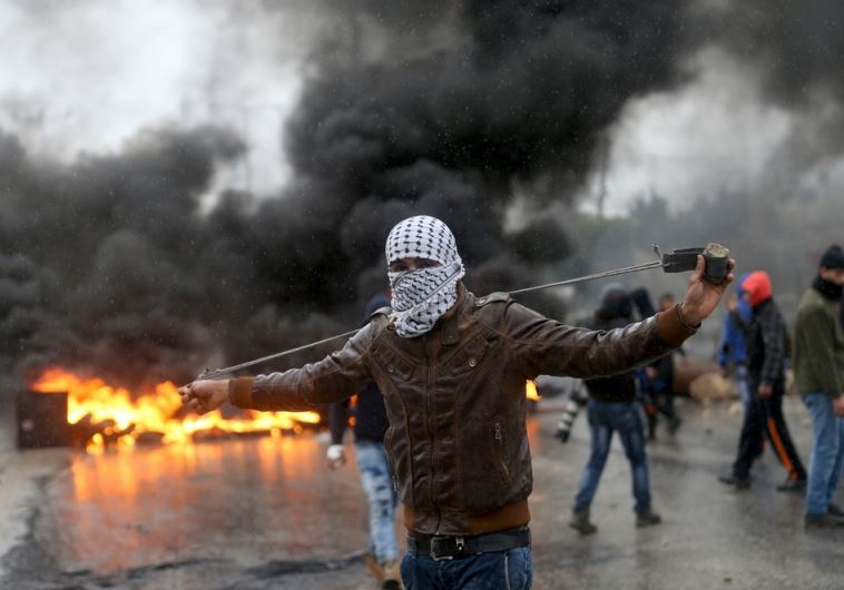 A Palestinian protester prepares his sling to hurl stones towards Israeli troops