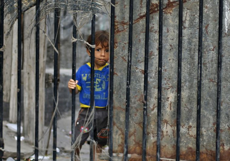 A Palestinian boy looks through the gate of his family's house at Shatti (beach) refugee camp in Gaz