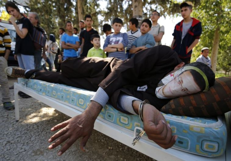 A Palestinian man in Ramallah lies on a bed wears a face covering depicting Mohammed al-Qiq