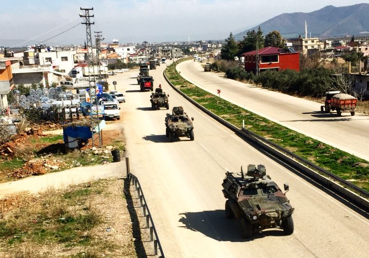 Turkish military vehicles drives through a town near the Syrian border