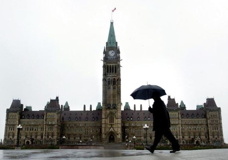 A pedestrian walks in the rain on Parliament Hill in Ottawa, Canada.