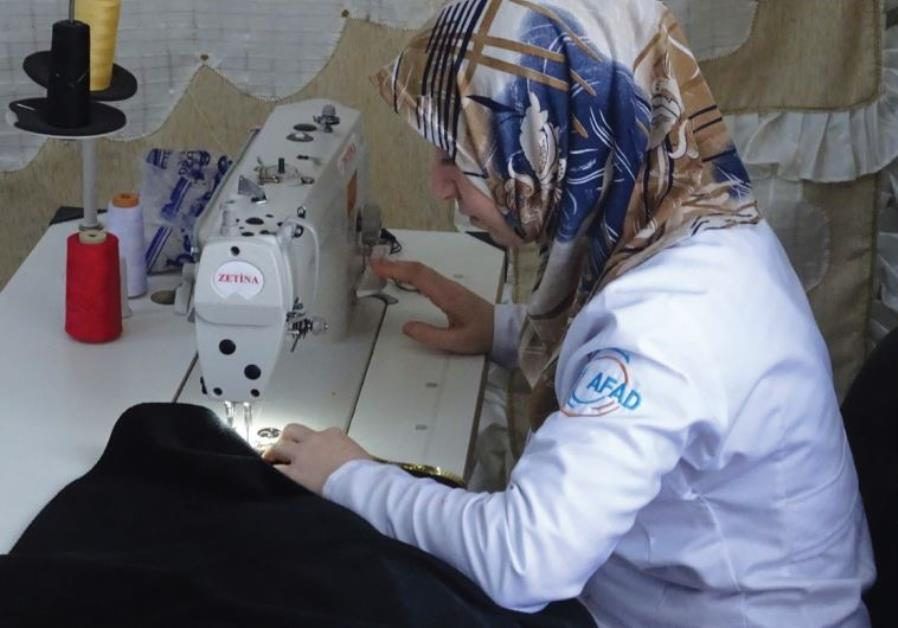 A WOMAN works at a sewing station in the Oncupinar refugee camp near Kilis.