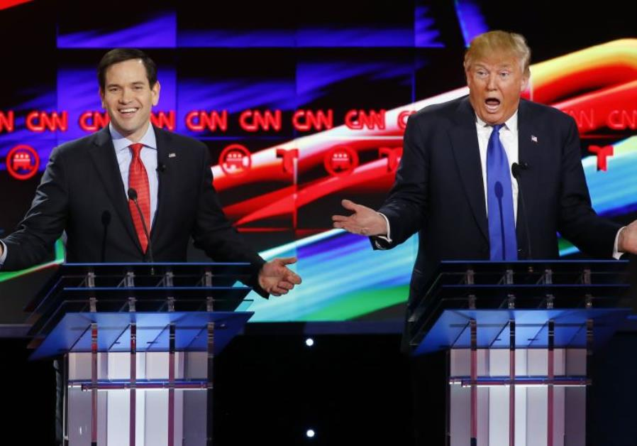 Republican US presidential candidates Marco Rubio (L) and Donald Trump speak simultaneously at the d