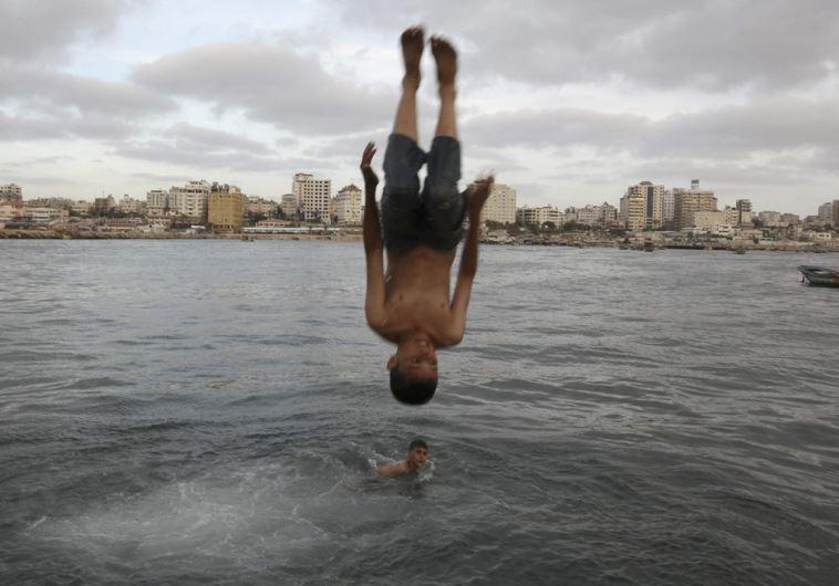 A Palestinian boy jumps into the sea at Gaza Seaport in Gaza City