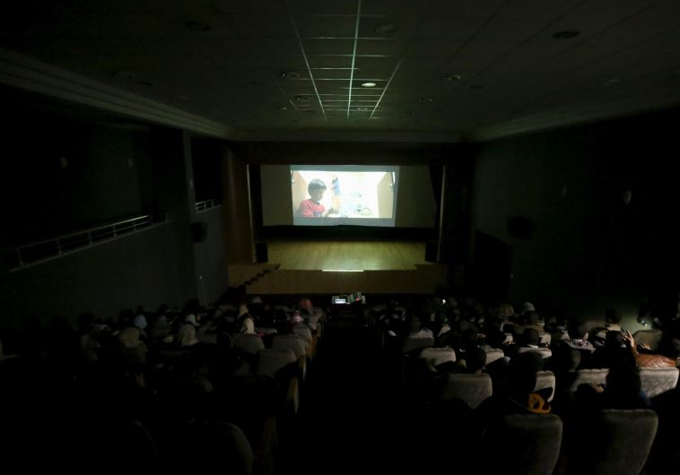 Palestinian spectators watch a movie at Red Crescent Society hall in Gaza City February 25, 2016.