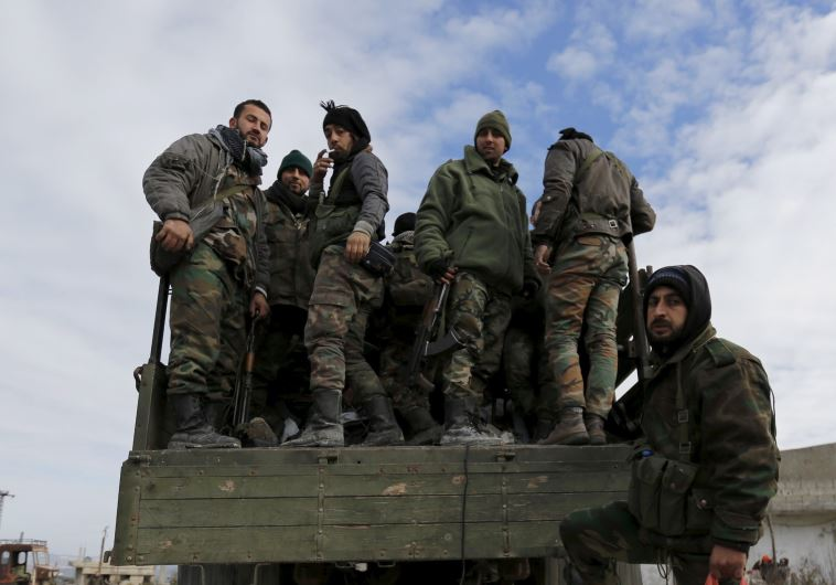 Forces loyal to Syria's President Bashar al-Assad stand on a military truck in the town of Rabiya