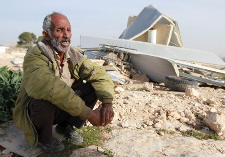 A Palestinian man sits next to the remains of his dwelling after it was demolished by Israeli forces