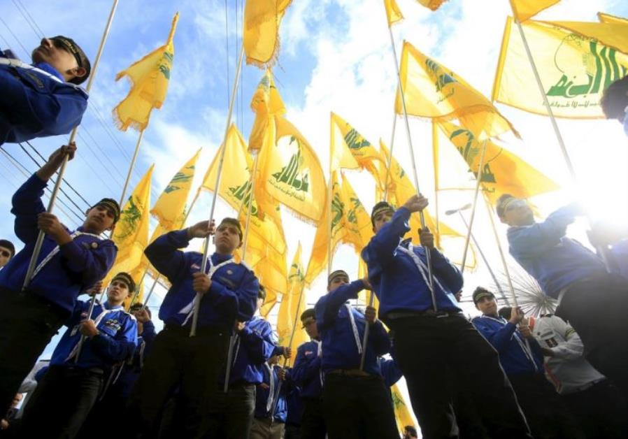 Lebanon's Hezbollah scouts carry their parties flag while marching at the funeral of 3 Hezbollah men