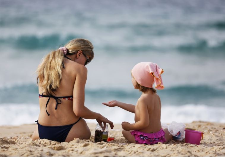 A woman and a girl sit in front of the Mediterranean at the beach in Ashkelon