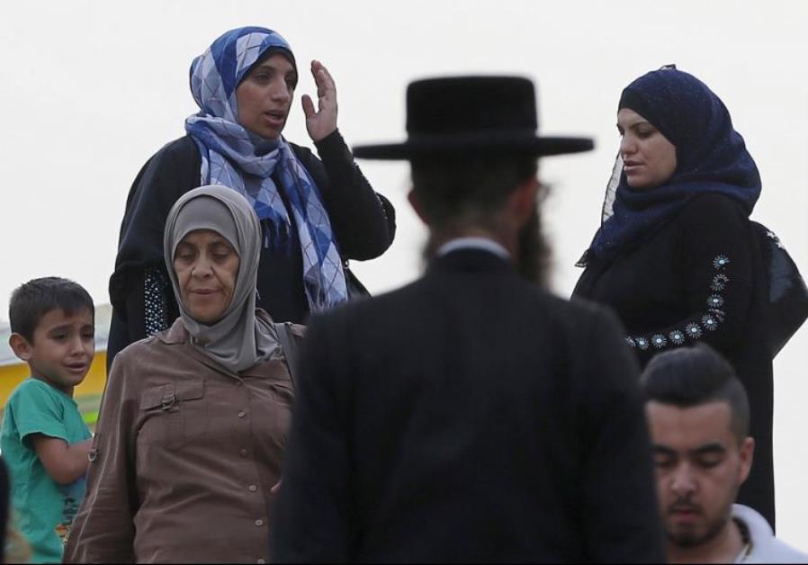 An ultra-Orthodox Jewish man walks next to Palestinian women in Jerusalem's Old City