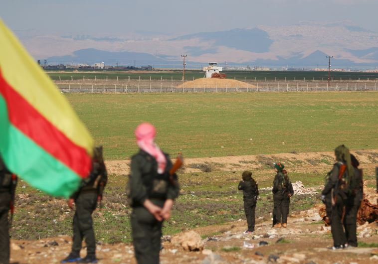 Kurdish members of the Self-Defense Forces stand near the Syrian-Turkish border in the Syrian city o