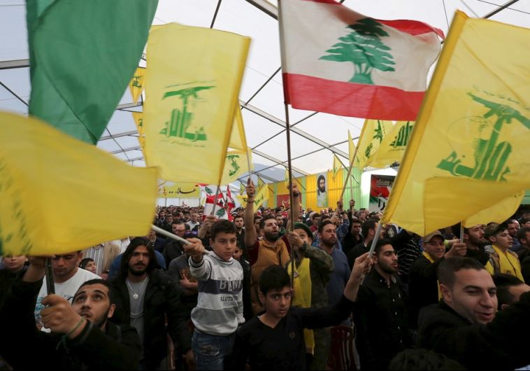 Supporters of Lebanon's Hezbollah leader Hassan Nasrallah wave Hezbollah and Lebanese flags
