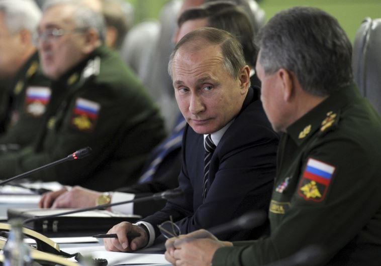 Russian President Vladimir Putin looks at Defence Minister Sergei Shoigu