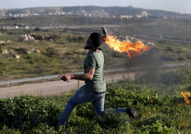 A Palestinian protester hurls a Molotov cocktail towards Israeli troops during clashes