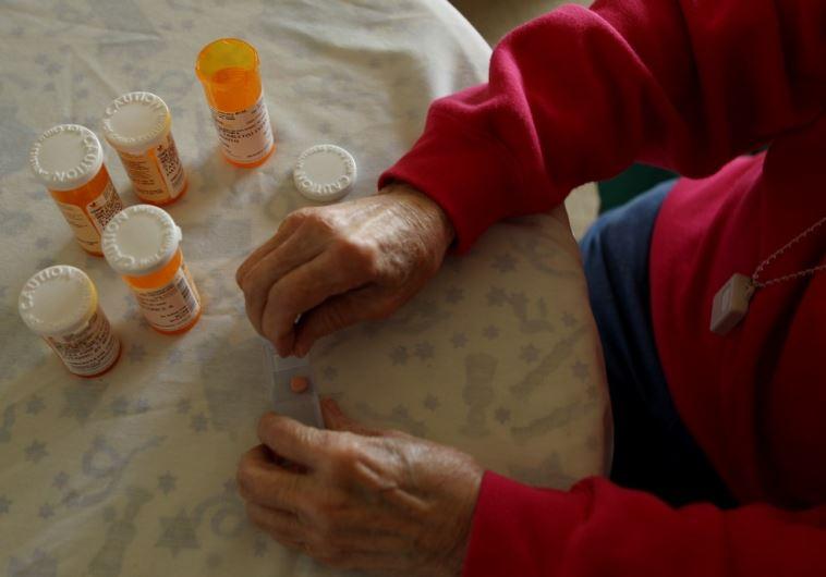 A senior citizen sorts her daily medical prescriptions
