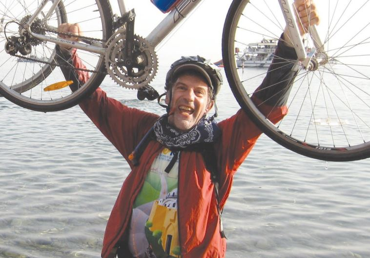 FRANKLYN D. MEDJUCK holds up his bicycle in Eilat at the end of the Hazon Bike Ride marathon he did